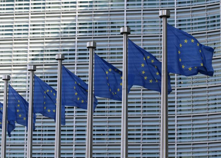 Symbolbild mit EU-Flaggen vor einem Gebäude der EU.